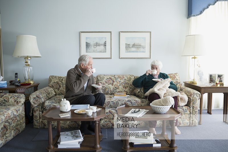Senior couple drinking tea and knitting in living room