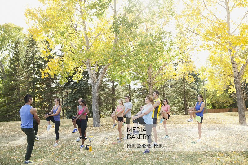 Outdoor fitness class stretching together.