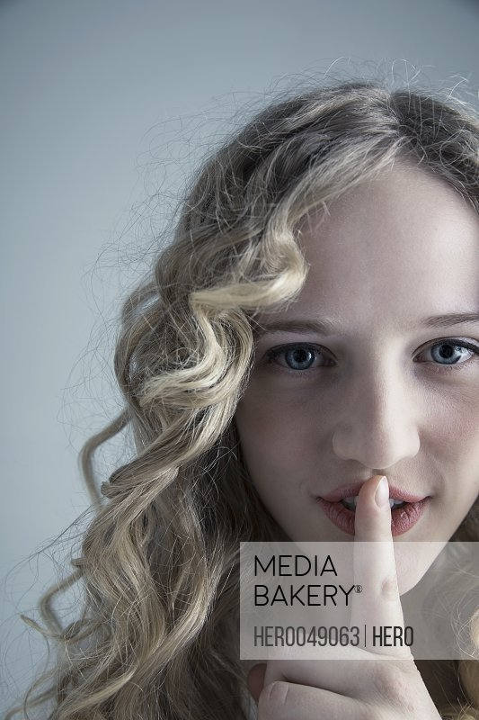 Close up portrait Caucasian young woman with curly blonde hair gesturing shhh