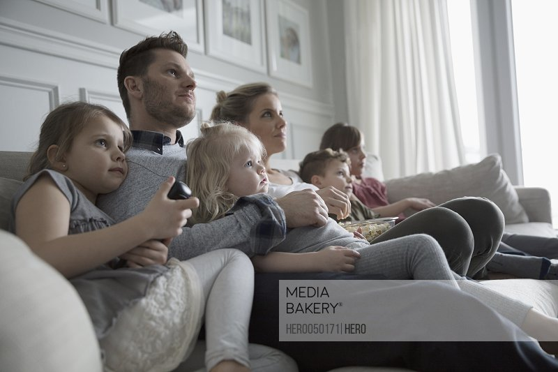 Photo by Hero Images - Young family watching TV on living room sofa