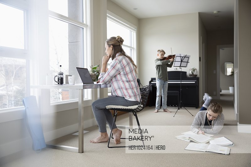 Mother working from home while children study and practice violin