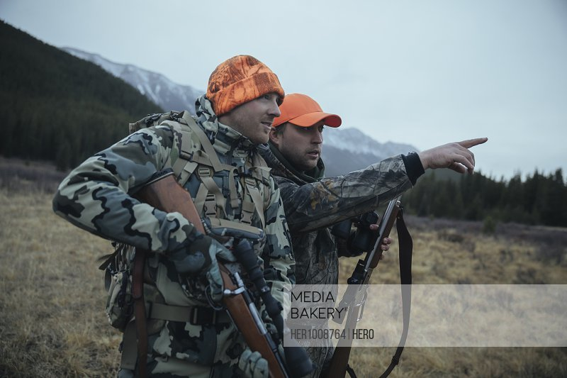 Male hunter friends in camouflage with hunting rifles pointing in remote field