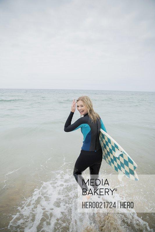 Portrait blonde female surfer with surfboard wading ocean
