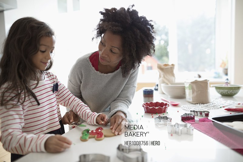 Mother and daughter decorating Christmas gingerbread cookies in kitchen