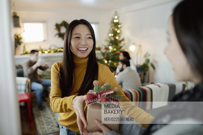 Happy young woman greeting friend with Christmas gift in doorway