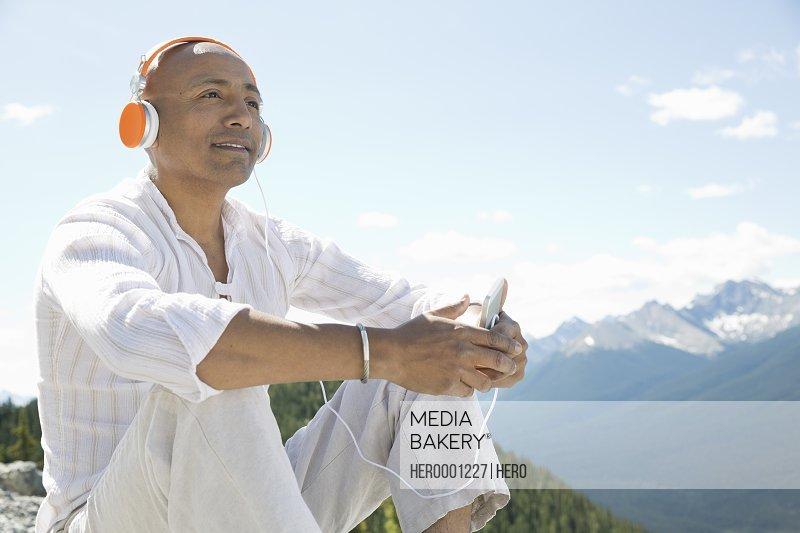 Mature man listening to music outdoors