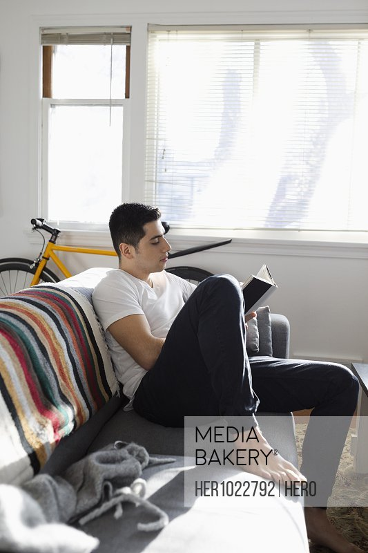 Young Latinx man relaxing, reading book on sofa