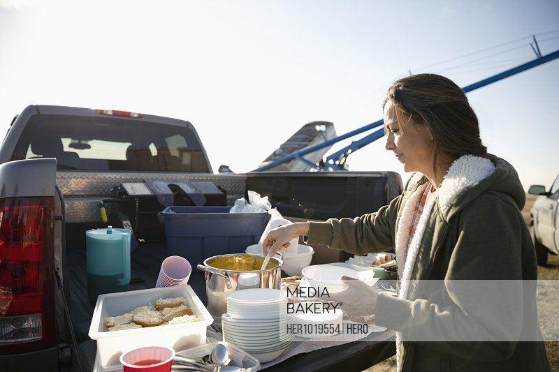 Female farmer serving lunch at pickup truck bed on sunny farm