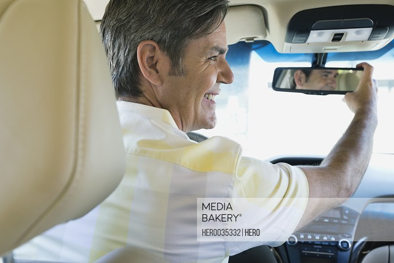 Smiling man adjusting rear-view mirror in car