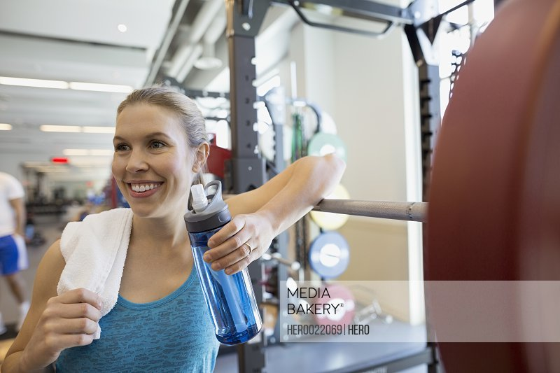 Smiling woman drinking water at barbell in gym