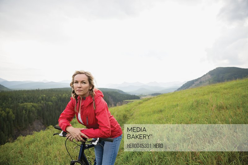 Portrait serious woman leaning on mountain bike in remote rural field