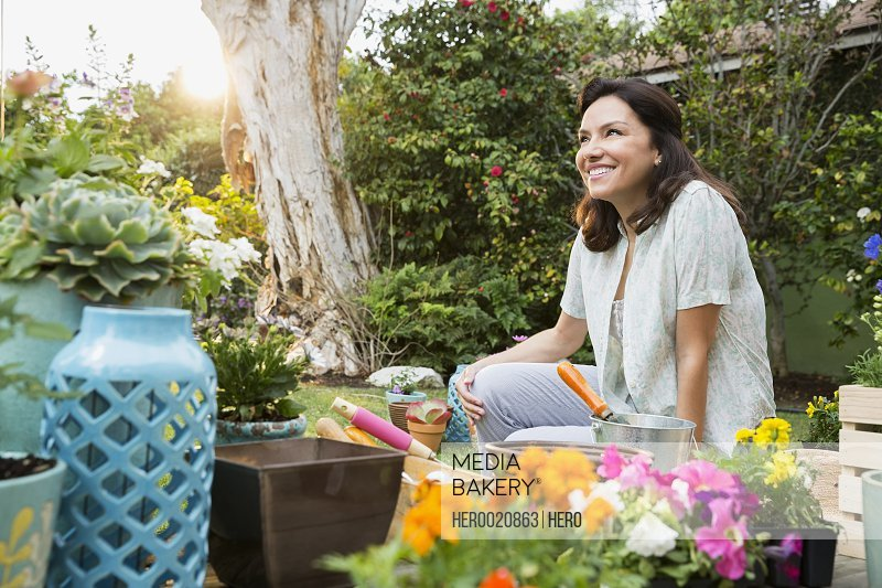 Smiling brunette woman planting flowers in sunny backyard