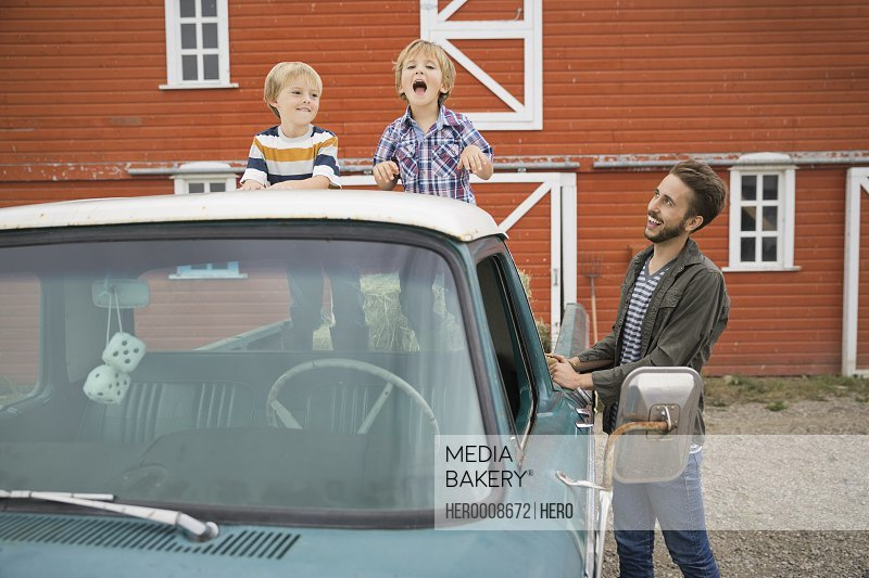Man looking at children standing on pick-up truck
