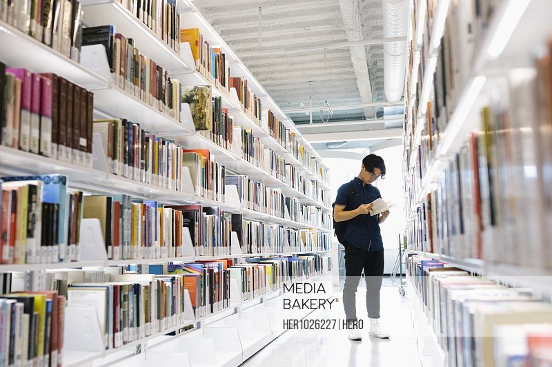 Student standing between bookcases and reading in univerity library
