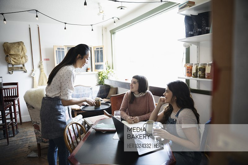 Waitress serving coffee to women working in cafe
