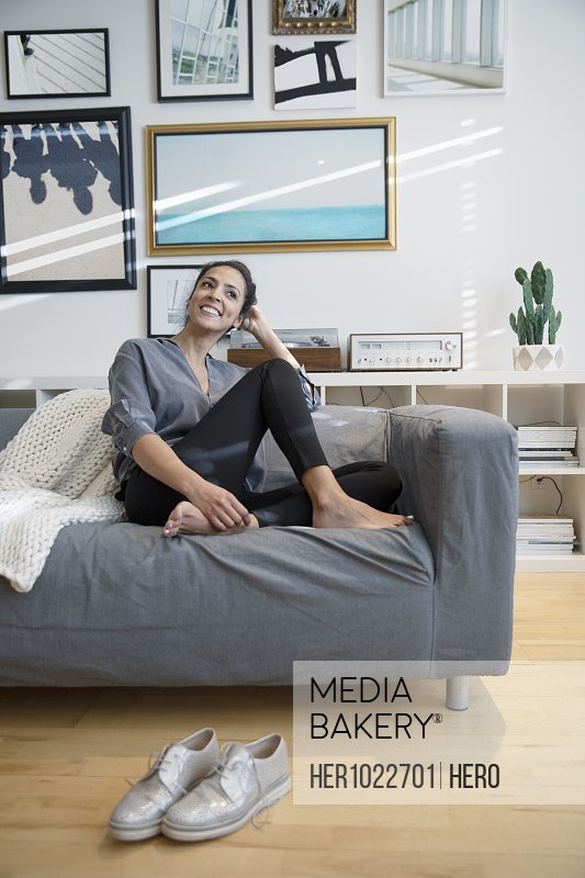 Happy barefoot woman relaxing on living room sofa