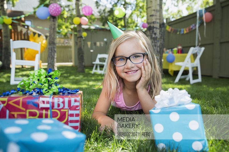 Portrait smiling girl birthday party hat gifts grass