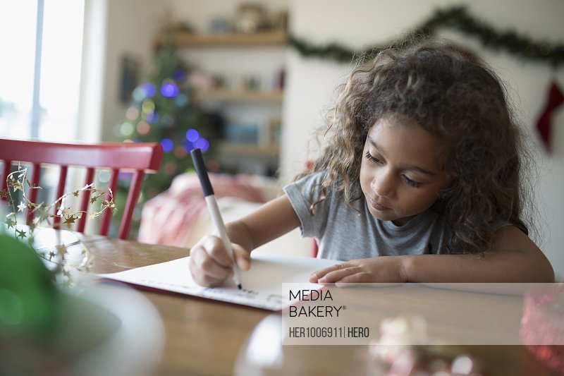 Girl writing Christmas letter to Santa at dining table