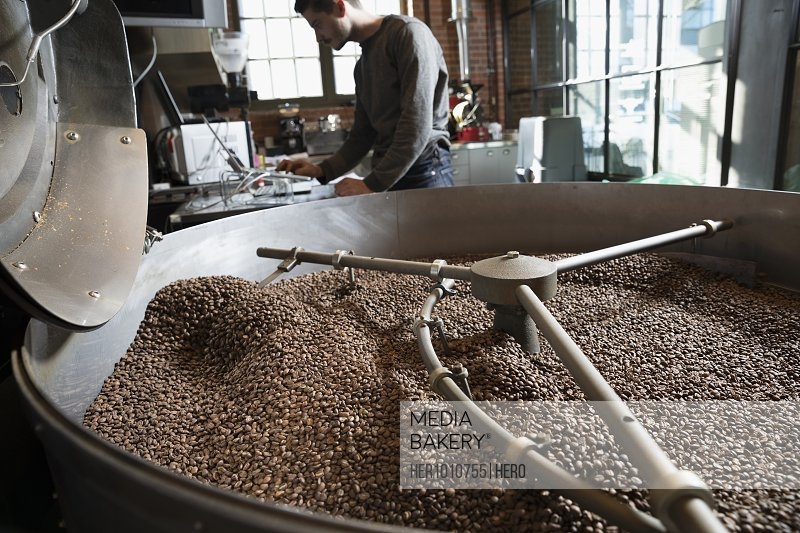 Coffee beans roasting in large coffee roaster