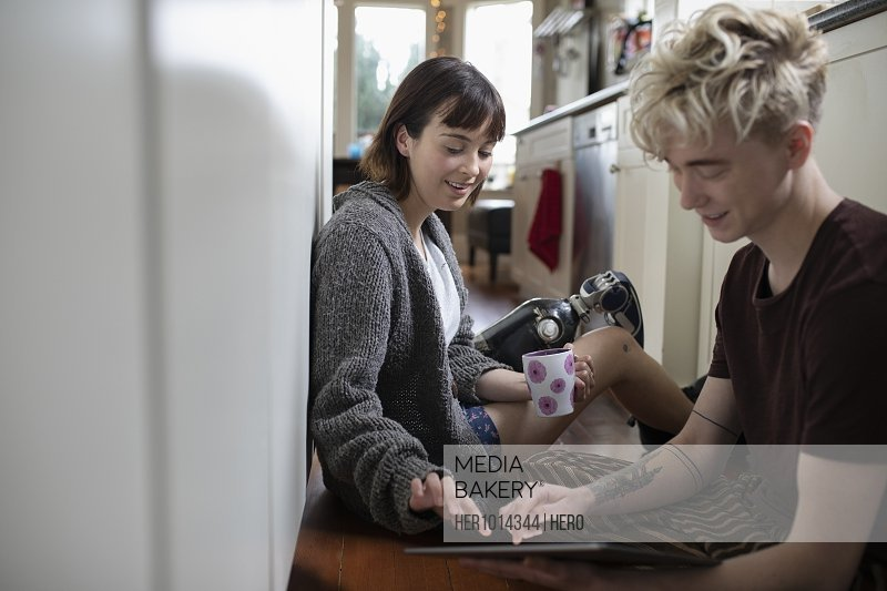 Young woman amputee drinking coffee, using digital tablet with boyfriend on kitchen floor