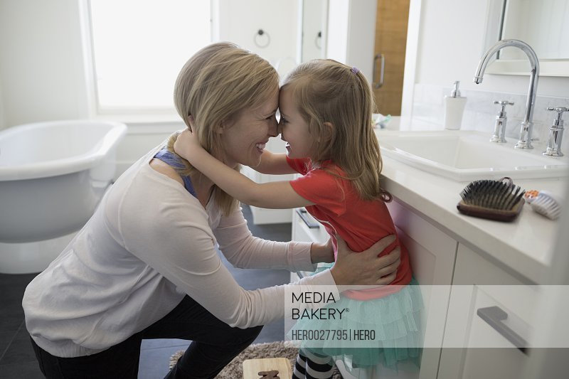 Affectionate mother and daughter rubbing noses in bathroom