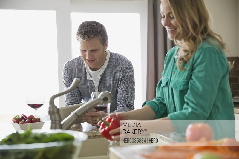 Woman washing vegetables in kitchen while husband uses digital tablet