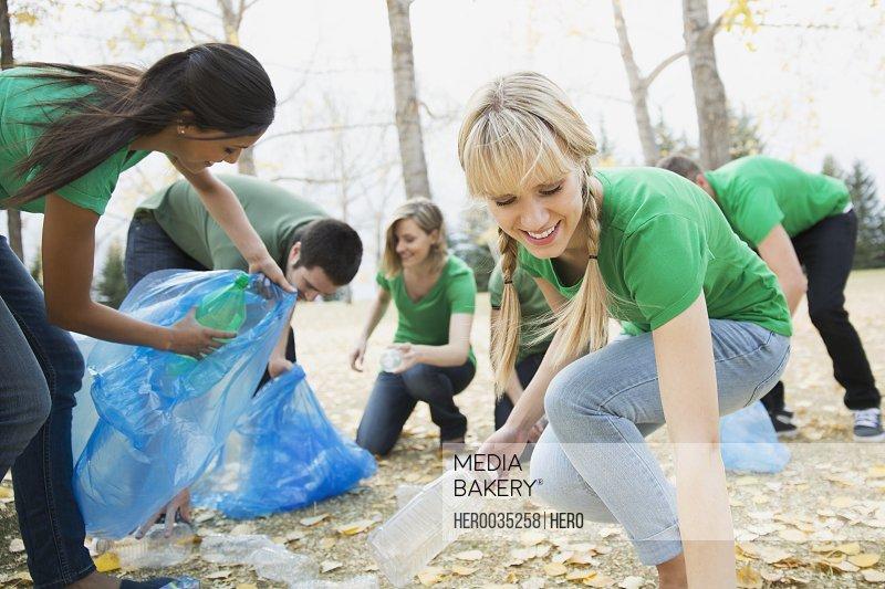Group of volunteers collecting bottles in plastic bags