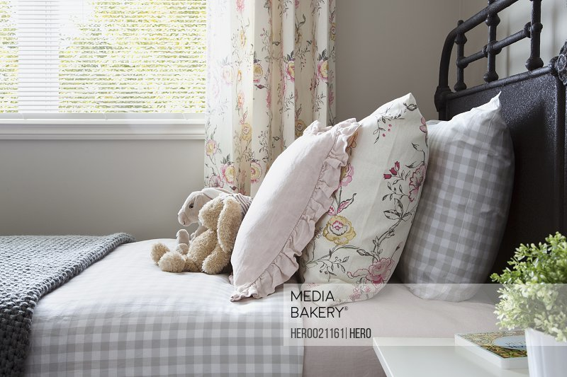Pastel and gingham pillows on bed stuffed animals
