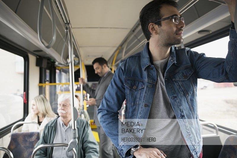 Man standing riding bus