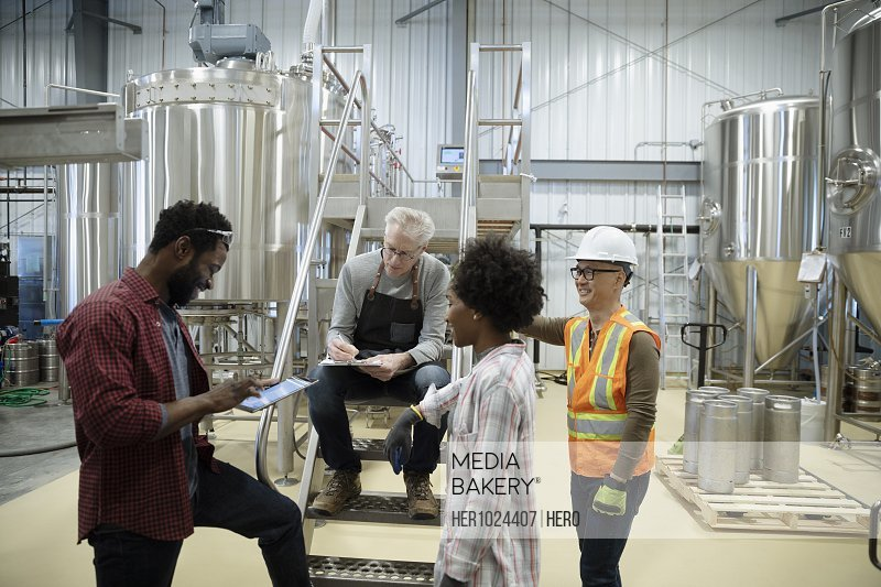 Brewers with digital tablet meeting in brewhouse distillery