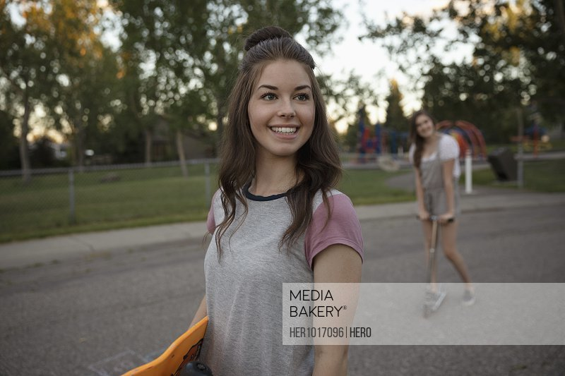 Smiling young woman with skateboard on street