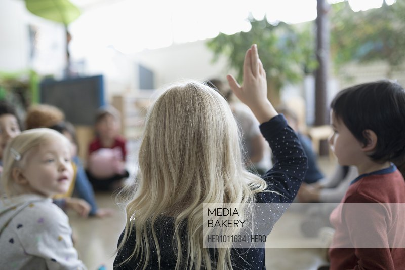 Preschool girl student raising hand in classroom