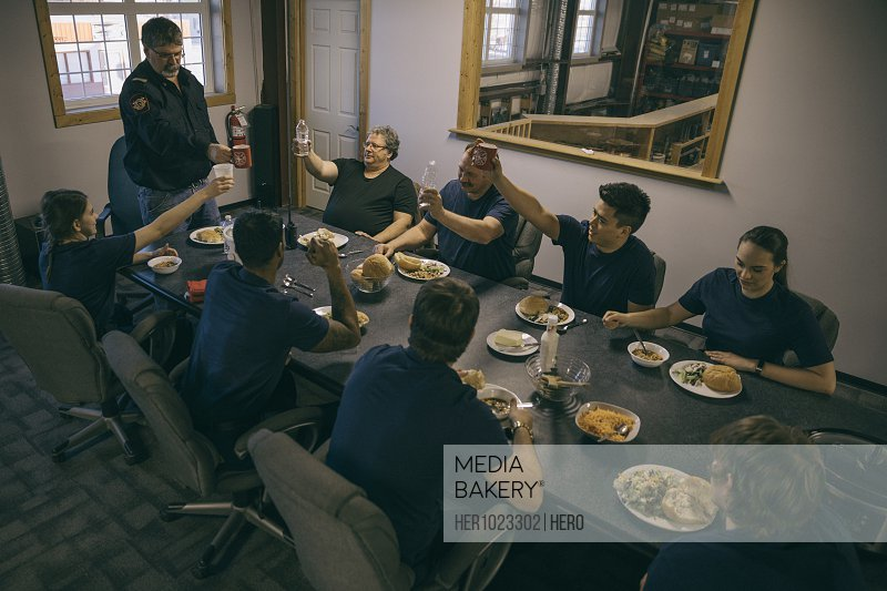 Firefighters eating dinner, toasting glasses in fire station