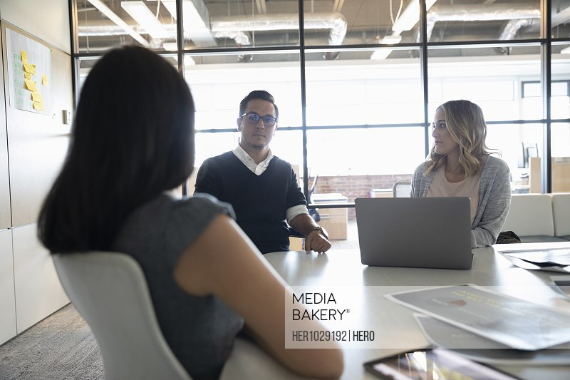 Businessman listening to female colleagues in meeting