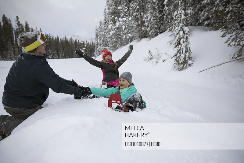 Playful family snowshoeing in snow