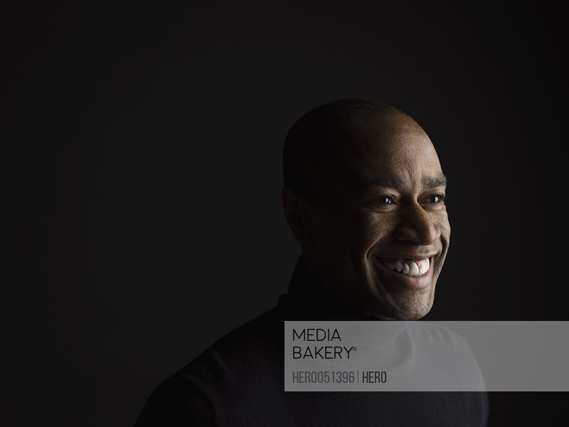 Portrait smiling African American man looking away against black background
