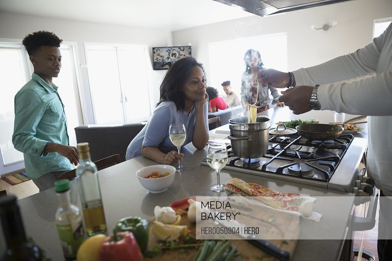 African American family cooking and drinking white wine in kitchen