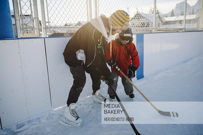 Father teaching son how to play outdoor ice hockey