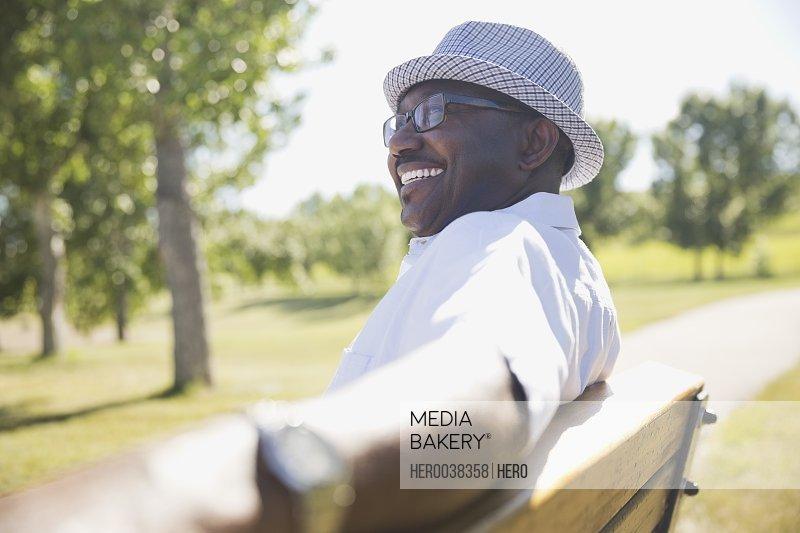 Smiling senior man sitting on park bench