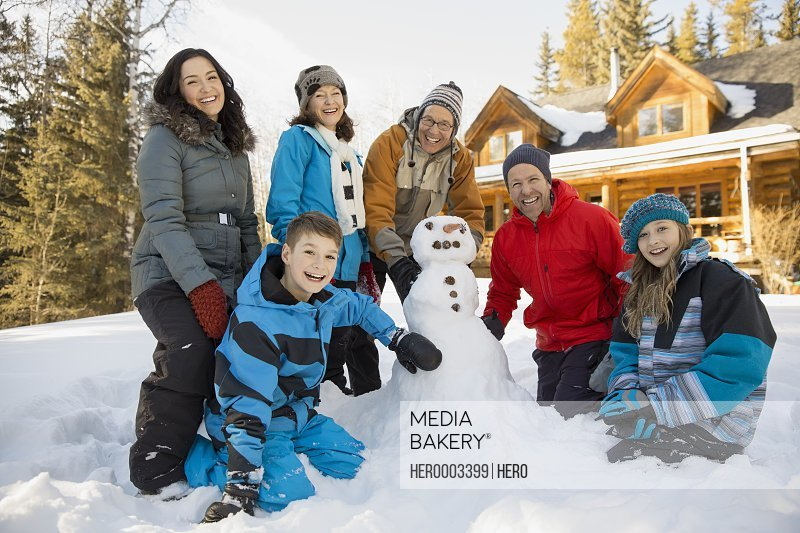 Three generation family building snowman