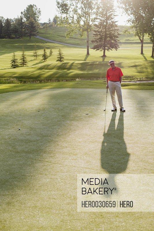 senior male golfer standing on green creating long shadow