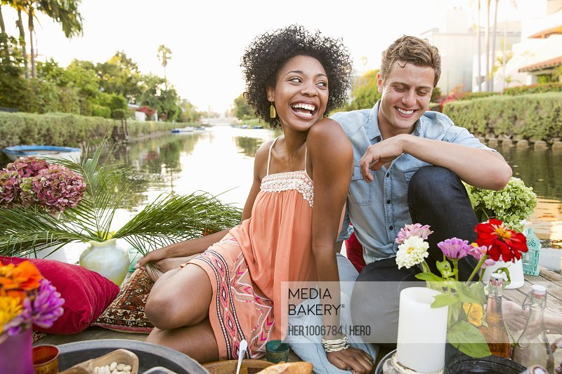 Laughing young couple enjoying romantic picnic on raft with flowers on summer lake
