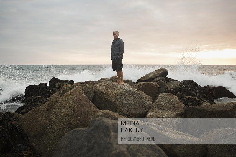 Ocean splashing rocks behind man at sunset