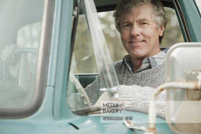 portrait of middle-aged man sitting in old truck