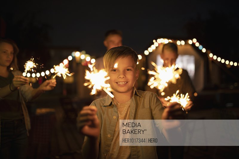 Portrait smiling boy playing sparklers
