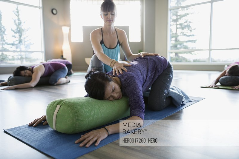 Instructor stretching womans back in restorative yoga class