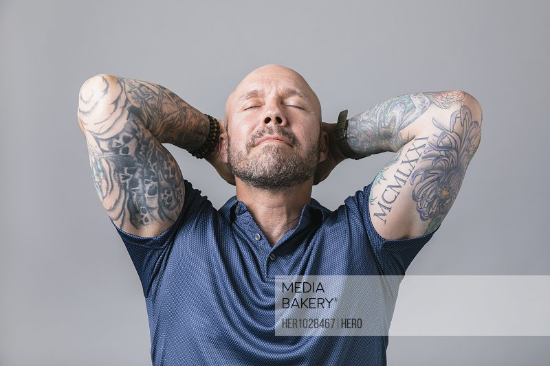 Portrait serene man with tattoos covering arms