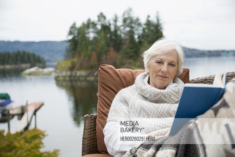 Senior woman relaxing reading book lakeside patio