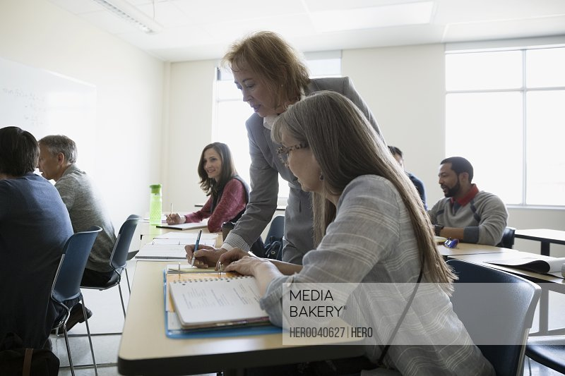 Professor helping adult education student in classroom