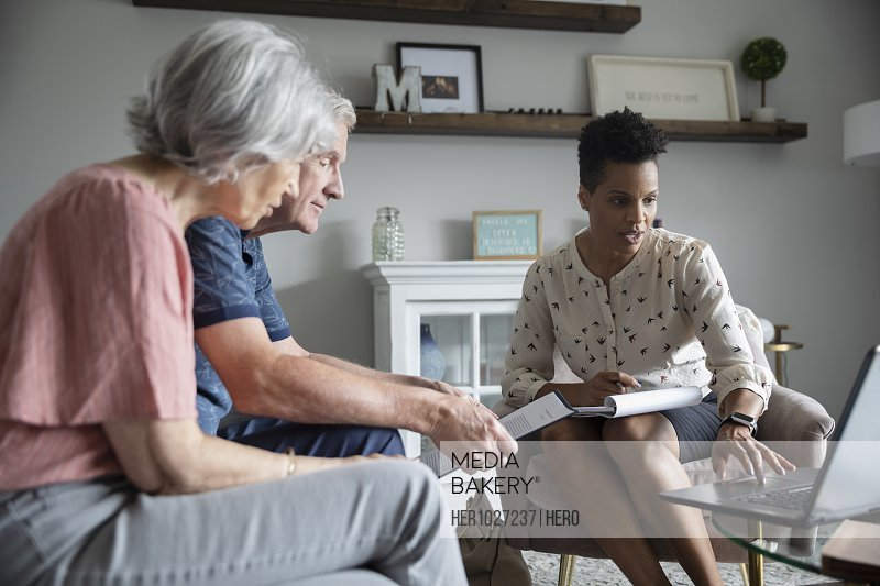 Financial advisor with laptop meeting with senior couple in living room